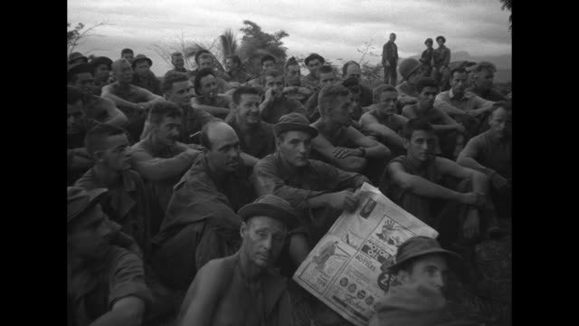 vs numerous american soldiers seated on the ground listen to a portable radio / vs the men play poker on a blanket using spent cartridge shells as... - newsreel stock videos & royalty-free footage