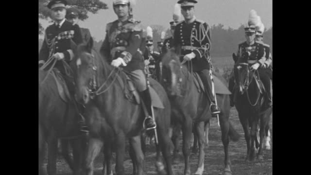 numerous caucasian military figures ride on horseback / vs emperor hirohito saluting from white horse, riding with entourage toward ceremony at which... - 昭和天皇点の映像素材/bロール