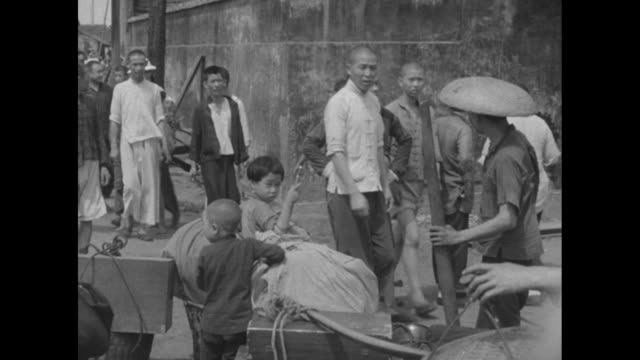 numerous chinese civilian men wearing a variety of hats / family seated on outdoor table eating a meal / vs people walking past children and bundles;... - emigration and immigration stock videos & royalty-free footage