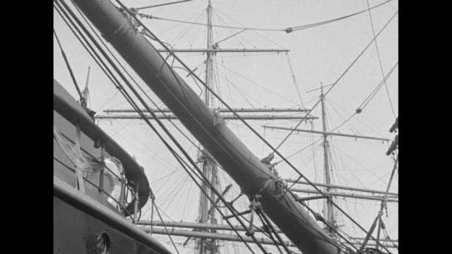numerous fishing boats at dock with a bow of a sundappled ship and a pan up into its rigging / men climb up the main mast to a bundled horizontal... - schiffsmast stock-videos und b-roll-filmmaterial