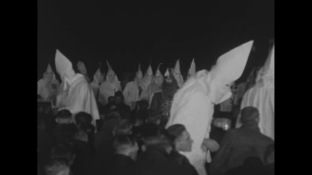 vídeos de stock, filmes e b-roll de numerous men in civilian clothes kneel as ku klux klansmen sprinkle them with water at outdoor nighttime ceremony a group of men stand nearby in... - ku klux klan