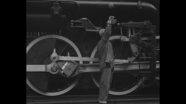vidéos et rushes de numerous men on and around locomotive / engineer with oil can / slide rods start to move wheels / the engine rolls past corner of building with men... - locomotive