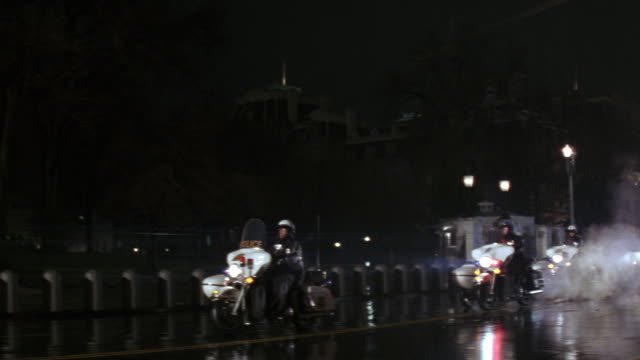 ms numerous security vehicles and police cars/automobiles with flashing lights atop, moving through rainy street / washington d.c., united states - motorcade stock videos & royalty-free footage