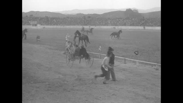 numerous shots of cowboys coming out of the gates riding bucking horses and bulls / note exact month/day not known - bocksprång bildbanksvideor och videomaterial från bakom kulisserna