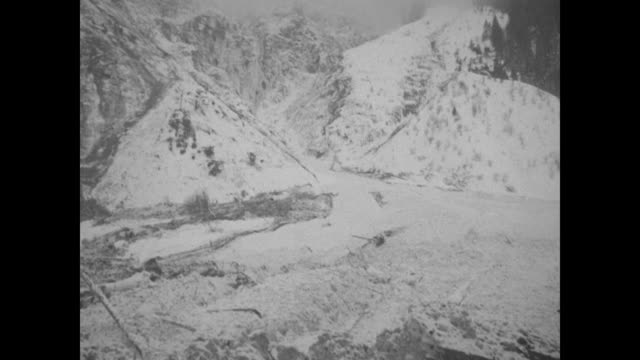 numerous shots of partially snow-covered buildings and wreckage in valley with mountains beyond / as solemn villagers look on, men dig in deep trench... - tape measure video stock e b–roll