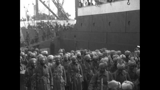 vs numerous sikhs walk down a gangplank from a transport ship and scores of them march forward from a bridge and walk the streets of the... - passing a note stock videos & royalty-free footage