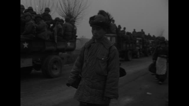 VS numerous soldiers trudging along dirt road with an ox and parked trucks filled with others looking on / Note exact day not known