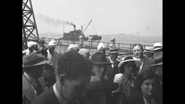 vidéos et rushes de numerous survivors including sikh men in summer attire depart from the ellis island ferry and step to a waiting bus, having survived a german attack... - robin day