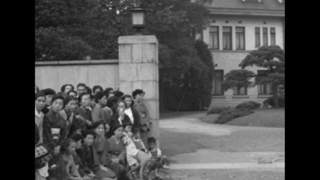 vídeos de stock, filmes e b-roll de numerous women and children gathered at gate to large house / children wave japanese flags with closeups of their faces / white woman and daughter /... - papel em casamento