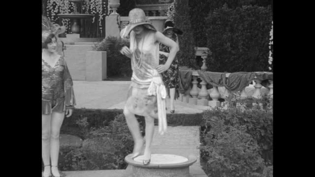 vidéos et rushes de numerous women in an elaborate garden setting / vs a woman stands on a turntable; three twirl at a fountain; the ladies all in fur coats with heavy... - 1920