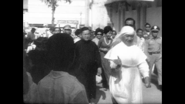 A nun and military personnel accompany Premier Nguyen Cao Ky and his wife Madame Ky as they arrive at a Saigon orphanage / smartly dressed girls with...