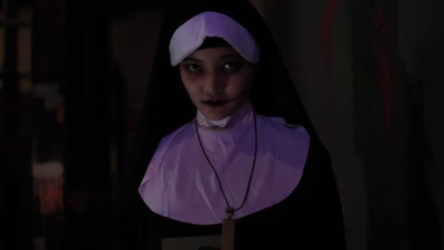 nun holding  religious cross in her hand halloween - nun stock videos & royalty-free footage