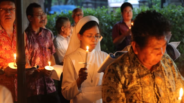 nun in her habit while singing during an easter service , the easter candle in hand .worship in a catholic church in yogyakarta in java in indonesia. - religious service stock videos & royalty-free footage