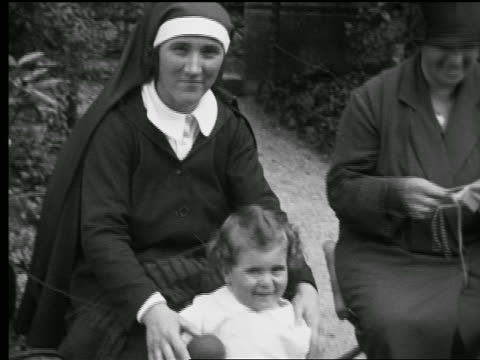 vídeos de stock, filmes e b-roll de b/w 1927 nun sitting in park next to other woman + holding toddler standing in front of her / paris - nun