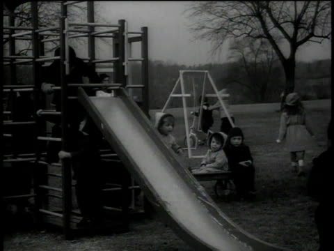 vídeos de stock, filmes e b-roll de 1946 ws nun supervising children sliding down a slide and playing - nun
