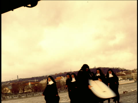 vídeos de stock, filmes e b-roll de peach nun swinging surfboard in circles as group of nuns run by / prague, czech republic - nun