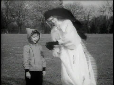 vídeos de stock, filmes e b-roll de 1946 ms nun talking to a boy and throwing a ball on a playground - nun