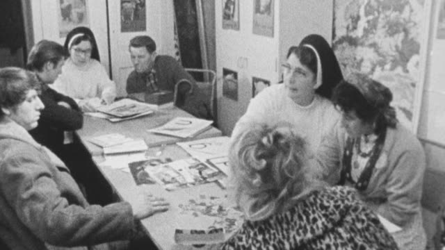 vídeos de stock, filmes e b-roll de 1972 montage nun teaching adult gypsies to read by cutting out and arranging letters of the alphabet / bushey, england, united kingdom - nun