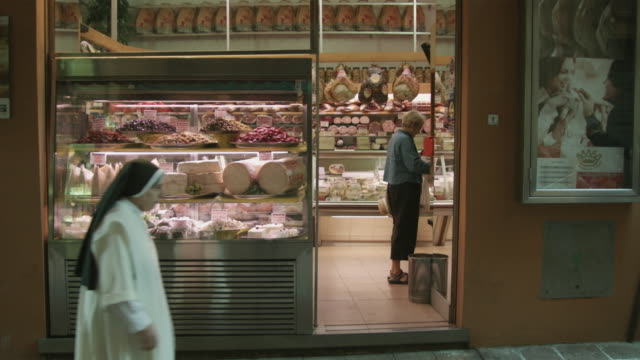 WS Nun walking past cheese shop, woman shopping inside / Bologna, Italy