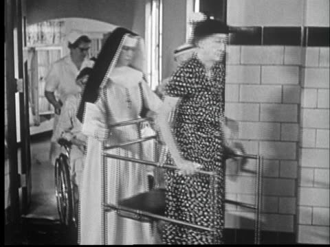 1959 MS Nuns and nurses assisting senior women walking through hall using walkers and  wheel chairs