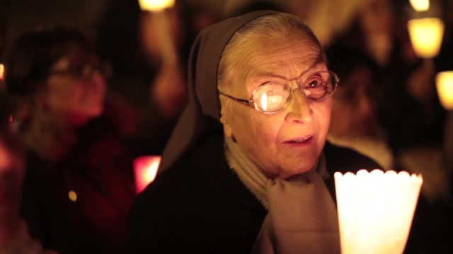 nuns and pilgrims having a candle lit vigil to give thanks to pope benedict xv1 on the eve of his retirement. general views around vatican city on... - eve biblical figure video stock e b–roll