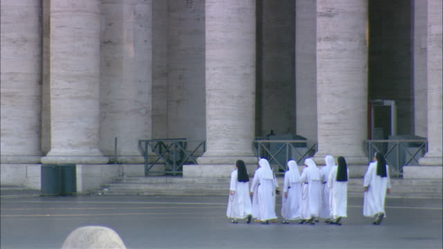 vídeos de stock, filmes e b-roll de nuns in habits pass a tourist in st. peter's square. - nun
