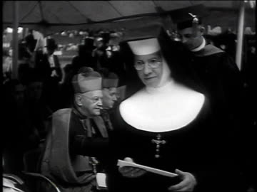 vídeos y material grabado en eventos de stock de nuns in procession at ceremony / nuns receiving diplomas from bishop / graduation ceremony on baseball field - escarapela