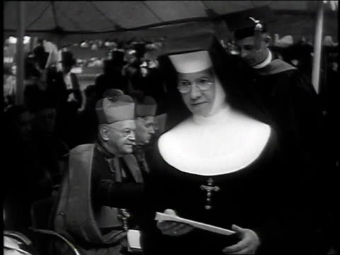 nuns in procession at ceremony / nuns receiving diplomas from bishop / graduation ceremony on baseball field - nun stock videos & royalty-free footage