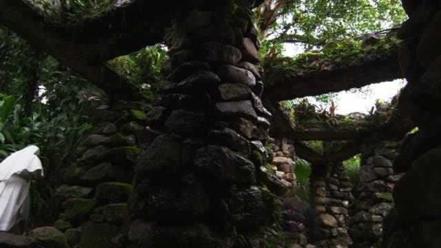 Nuns walking near stone structure columns in Botanico Jardins