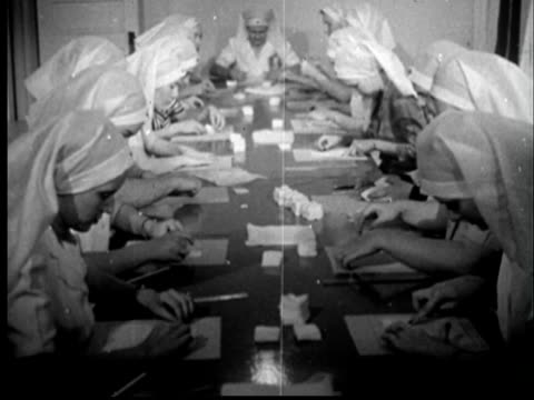 vídeos de stock, filmes e b-roll de 1945 film montage ms nuns working in two rows along length of table/ ms nuns working for the red cross, smiling and enjoying/ sylacauga, alabama - nun
