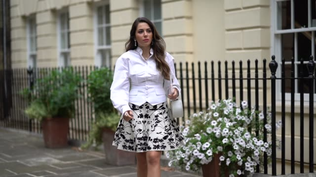 nurce erben wears earrings a white shirt a floral print skirt a semicircular bag with golden inserts white pointy shoes a sea shell anklet during... - gold coloured stock videos & royalty-free footage