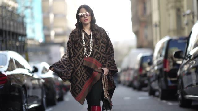 Nurce Erben wears sunglasses a Fendi logo poncho a necklace a Fendi bag red high leather boots during London Fashion Week February 2019 on February...