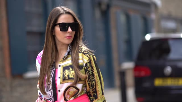 nurce erben wears sunglasses, a yellow and black shirt with printed patterns, a pink blazer jacket as a skirt, pink shorts, alexander mcqueen... - modedesigner stock-videos und b-roll-filmmaterial
