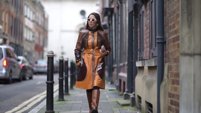 nurce erben wears sunglasses, an orange and brown leather long coat, a belt, a clutch, brown leather high boots, during london fashion week fall... - brown stock videos & royalty-free footage