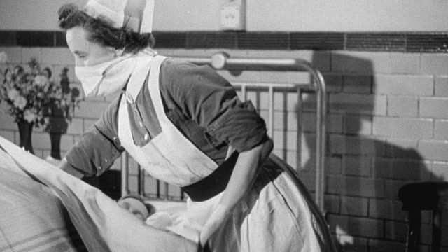 1949 montage nurse administering care to young polio patient lying in bed in hospital ward / united kingdom - polio stock videos & royalty-free footage