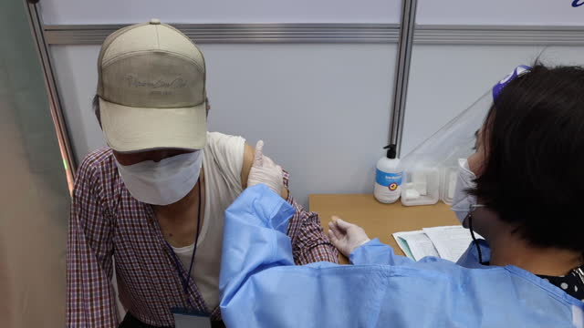 nurse administers a dose of the pfizer-biontech covid-19 vaccine at a vaccination site inside the guro arts valley theater in the guro district of... - 朝鮮半島点の映像素材/bロール