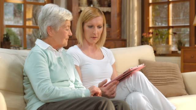 DS Nurse advising senior woman with help of tablet