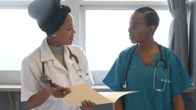 nurse and doctor discussing medical notes and agreeing - female nurse stock videos & royalty-free footage
