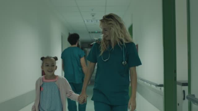 nurse and girl walking through hospital corridor - nurse walking stock videos & royalty-free footage