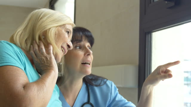 Nurse and patient talking while looking through window
