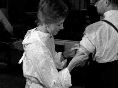 nurse applies a plaster to a mans arm following a flu vaccination shot. - bandage stock videos & royalty-free footage