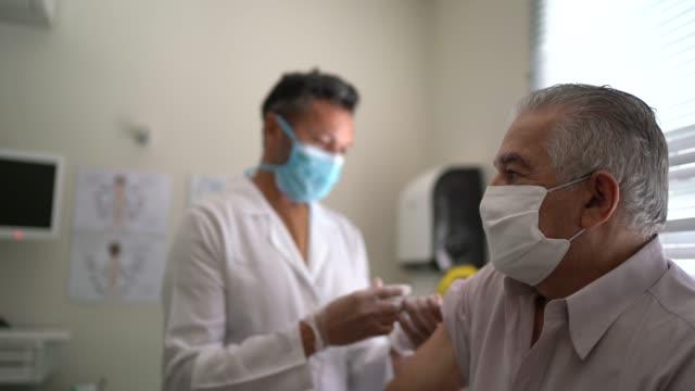 infermiera che applica il vaccino sul braccio del paziente - vaccini video stock e b–roll
