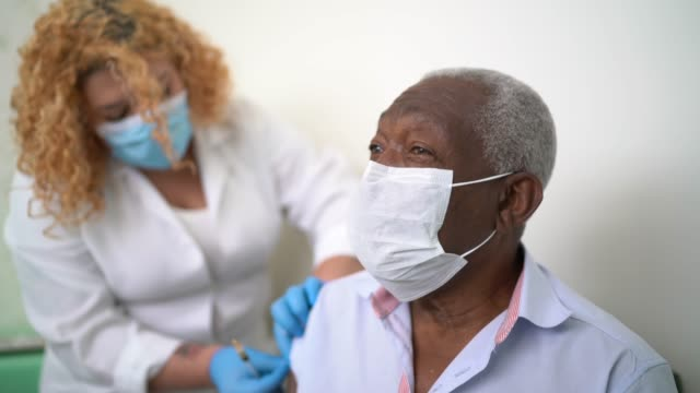 vídeos de stock, filmes e b-roll de enfermeira aplicando vacina no braço do paciente - vacina
