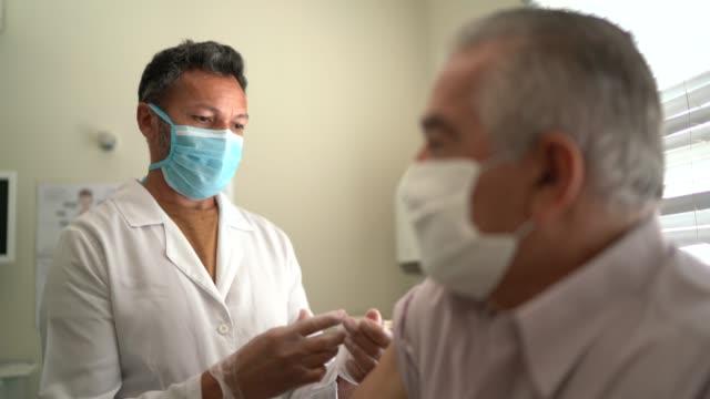 nurse applying vaccine on patient's arm - flu vaccine stock videos & royalty-free footage