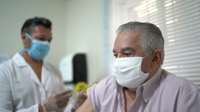 nurse applying vaccine on patient's arm - syringe stock videos & royalty-free footage