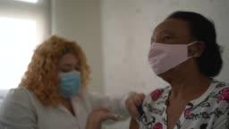 Nurse applying vaccine on patient's arm
