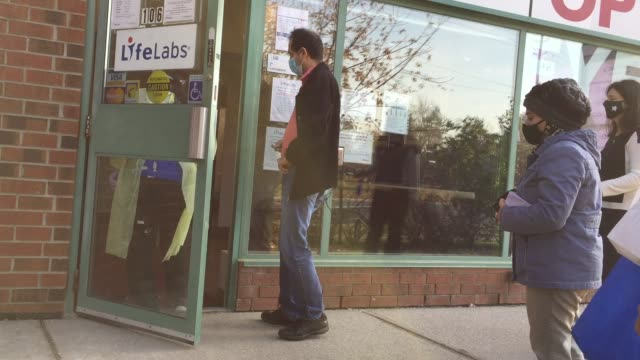 stockvideo's en b-roll-footage met nurse asks patients to answer covid-19 screening questions outside a medical office during the novel coronavirus in toronto, ontario, canada on... - toronto