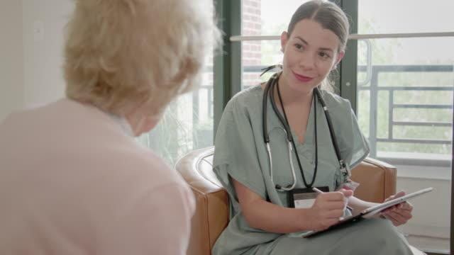 nurse asks senior woman questions using a digital tablert - visit stock videos & royalty-free footage
