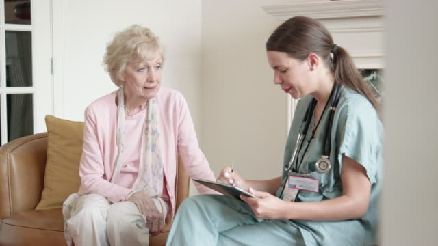 nurse asks senior woman questions using a digital tablert - healthcare worker stock videos & royalty-free footage