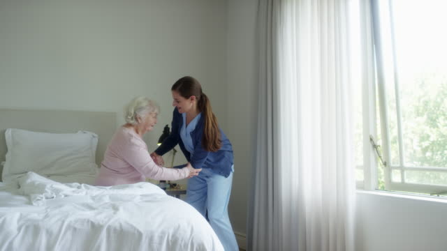 nurse assisting elderly woman in walking at home - sheltered housing stock videos & royalty-free footage